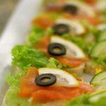 kanapki z łososiem, plasterkiem cytryny, czarną oliwką, i listkiem sałaty - usługi cateringowe