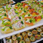 Patera dwupiętrowa: u góry znajdują się różne kanapki - z twarożkiem i ziołami, jajkiem, łososiem, serem pleśniowym, na dole babeczki z musem serowym i musem z szynki oraz roladki z łososiem - usługi cateringowe