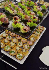 Dwupiętrowa patera: na górze znajdują się suszone śliwki owinięte w boczek i położone na liściu sałaty, na dole babeczki z musem serowym i szynkowym - usługi cateringowe