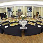 Catering Warszawa - Stoły zastawione daniami cateringowymi w owalnej sali na SGH