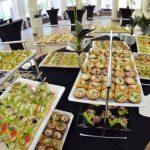 Stół ujęty z góry z róznymi potrawami cateringowymi ułożonymi na tacach - catering Warszawa