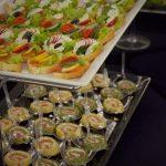 Catering dla firm warszawa - na górze patery: kanapki z twarożkiem ziołami oraz rzodkiewką, z warzywami i łososiem oraz z pieczonym indykiem i suszonymi pomidorami, na dole: tortilla z kurczakiem, tortilla wegańska z hummusem