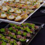 catering dla firm warszawa - na górze patery: tartinki z twarożkiem z ziołami i rzodkiewką oraz z z pieczonym indykiem i suszonymi pomidorami, na dole: śliwka zawijana w boczku