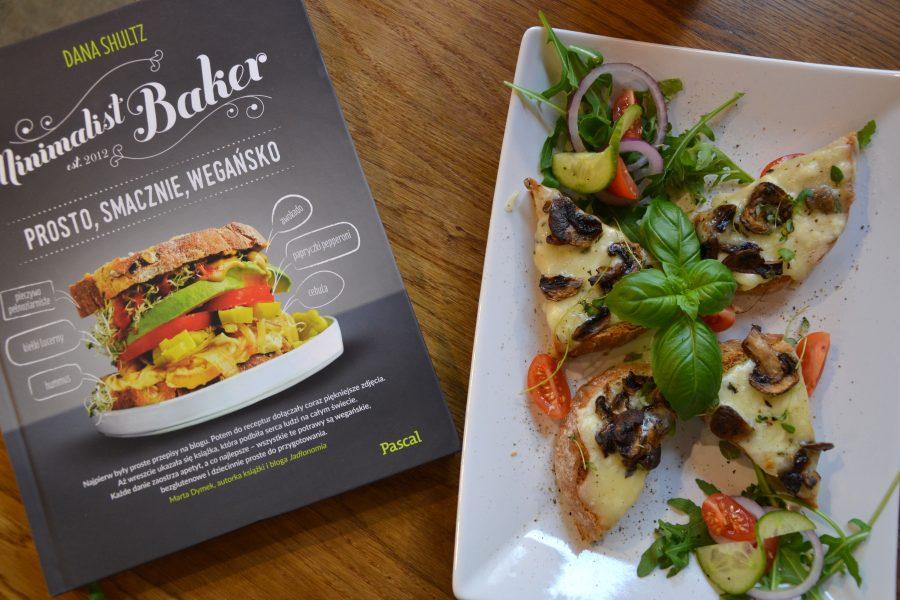 """Dobre śniadanie - grzanki z serem korycińskim i pieczarkami przystrojone rukolą, bazylią pomidorem i ogórkiem, obok książka """"Prosto, smacznie,wegańsko"""" Dany Shultz"""
